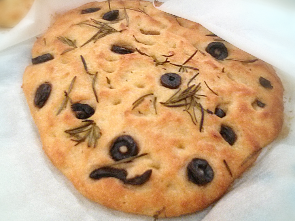 Gluten free focaccia with black olives, fresh rosemary, and olive oil.