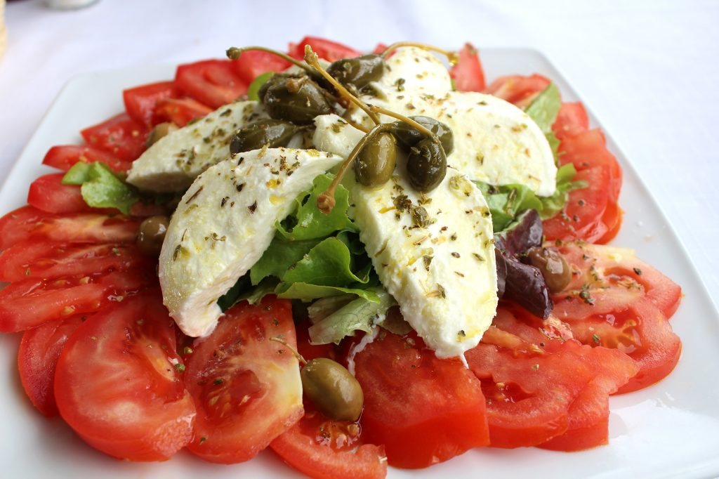 Caprese salad - Tomatoes, mixed leaves, basil, fresh mozzarella, olives, and capers.