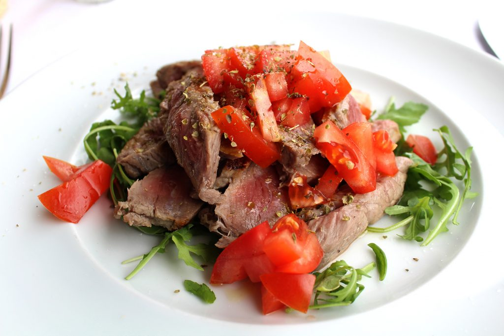 Grilled beef with rockets and tomatoes.