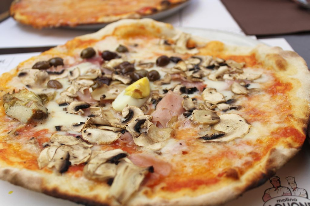Quattro stagioni - tomato sauce, fresh mozzarella cheese, organic artichokes, champignon mushrooms, ham, organic egg, and olives.