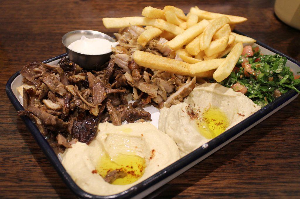 Shawa plate meal - chicken shawarma, hummus, baba ghanouj, toum (garlic sauce), tabbouleh salad & chips.