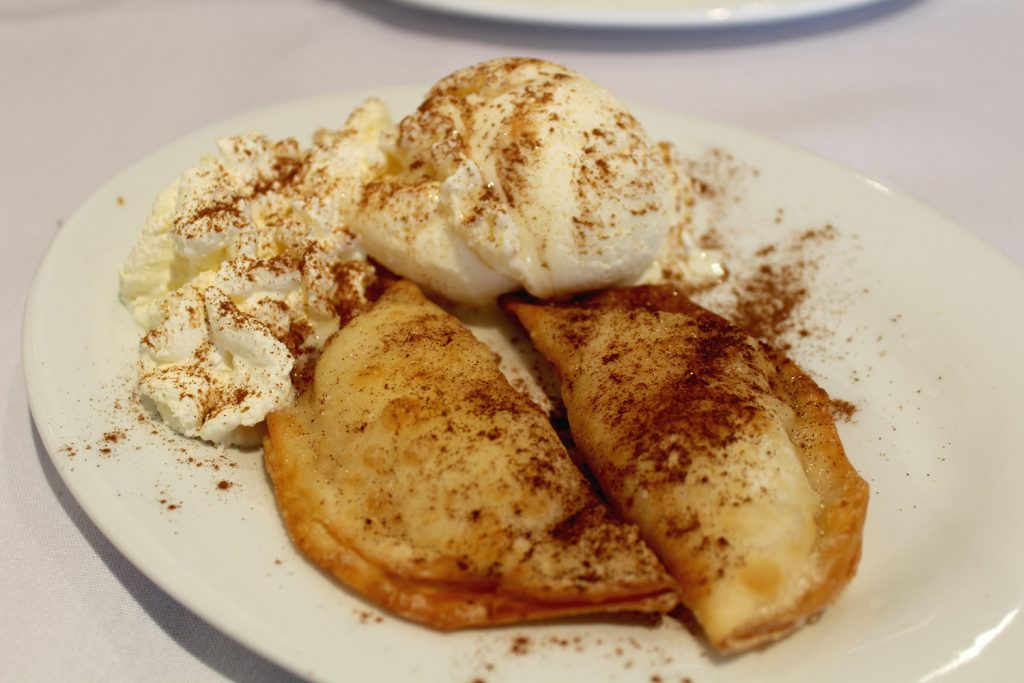 Bourekakia - home-made pastries filled with semolina custard, pan fried, and drizzled with syrup and cinnamon, served with ice cream and cream.