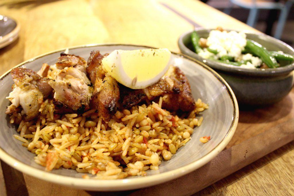 Spartan box with chicken, seasonal salad, smoky eggplant, and pilaf rice.