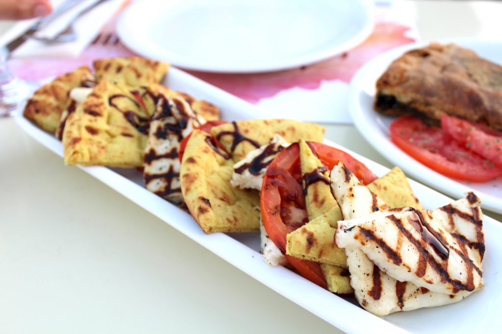 Grilled Haloumi, baked tomatoes, and pita bread in a balsamic dressing.