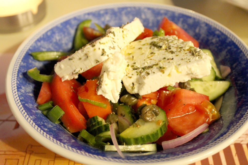 Greek salad - tomato, cucumber, olives, feta cheese, capers, onion, olive oil, and oregano.