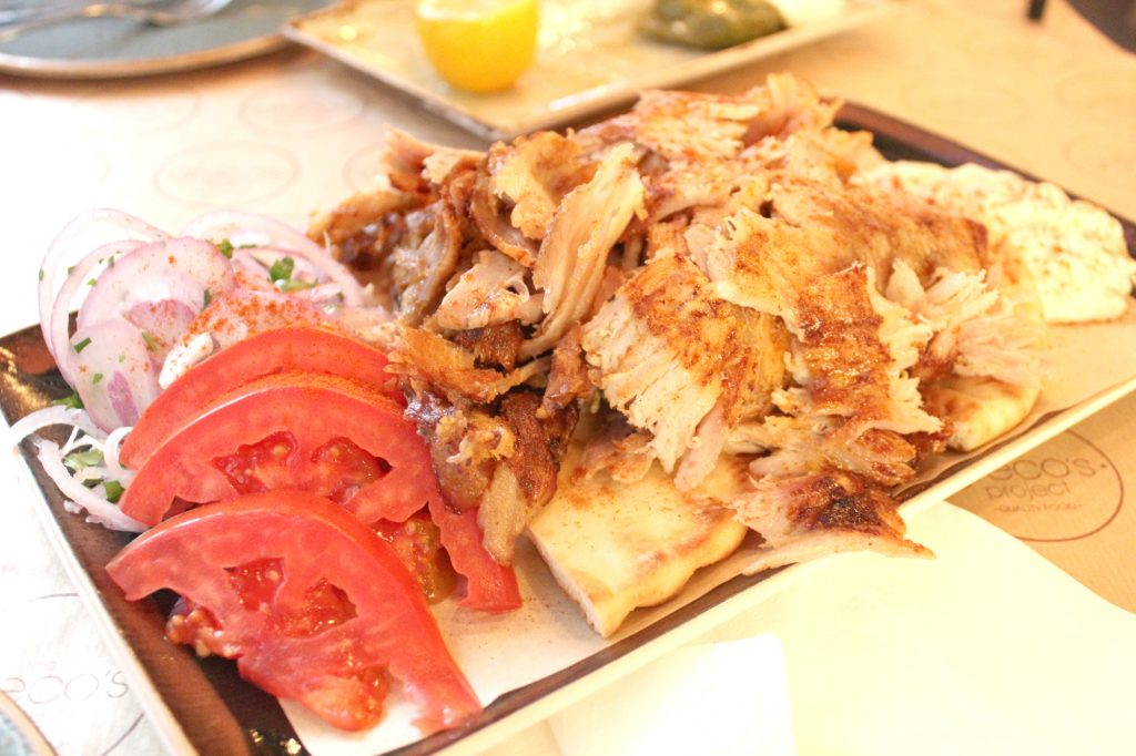 Pork Gyro platter - served with tzatziki sauce, tomato, onion, sweet paprika, and pita bread.