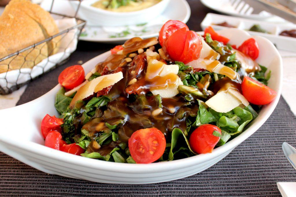 Santorini salad - lettuce, rucola, raisins, fresh onion, sun-dried tomatoes, pine seeds, parmegiano cheese, and special honey dressing.