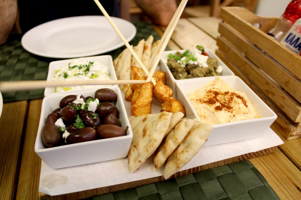 Chef's mezze board - Tzatziki, roasted eggplant dip, chilly feta cheese dip, marinated olives and feta, haloumi skewers, and grilled pita bread.