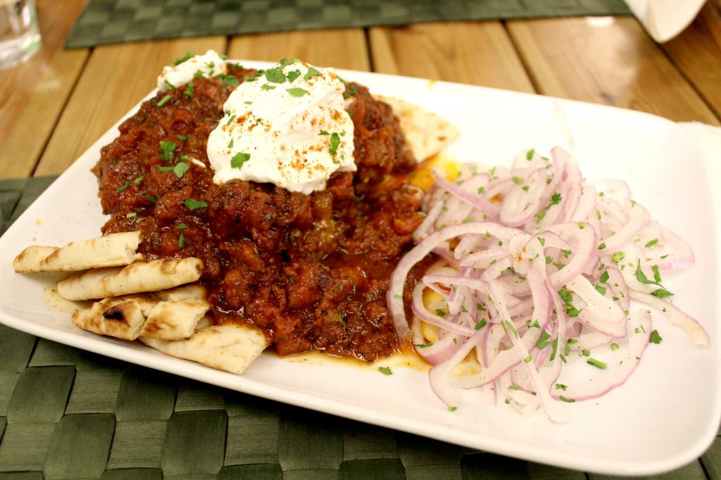 Lamb kofta in spicy tomato sauce, and Greek yogurt, served on pita bread.