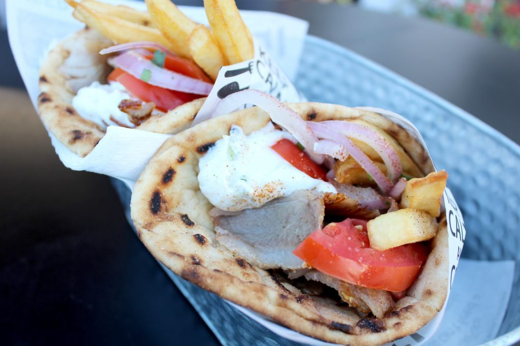 Pork gyro - served with hot chips, onion, tomatoes, and tzatziki sauce.