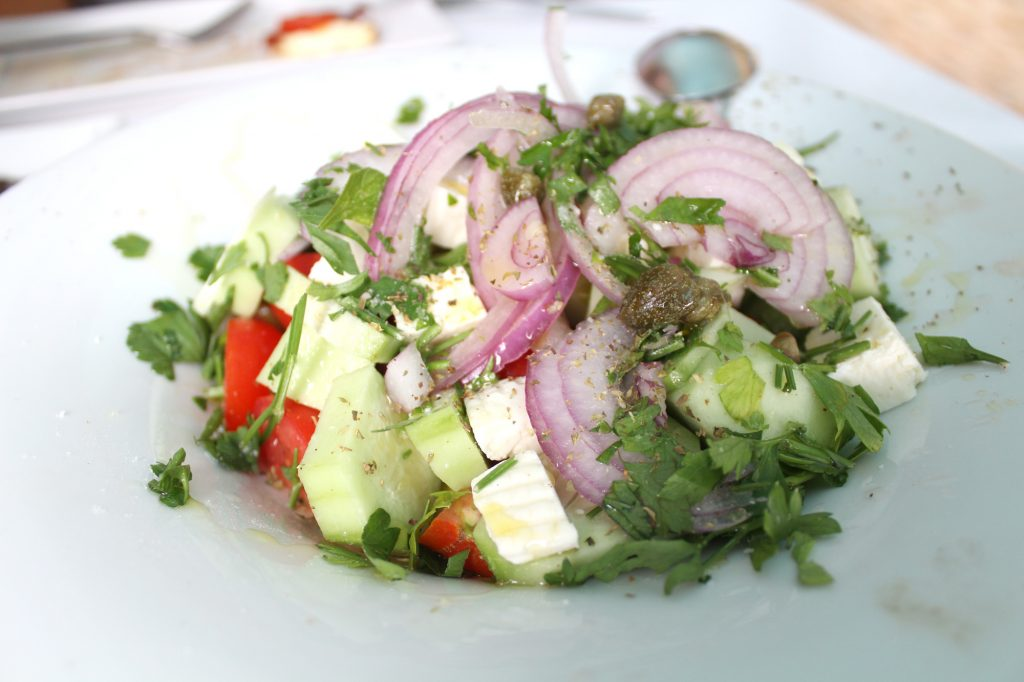 Santorini salad - Cherry tomaotes, cucumber, chloro (local white cheese), caper leaves, olives, onion, parsley, and olive oil.