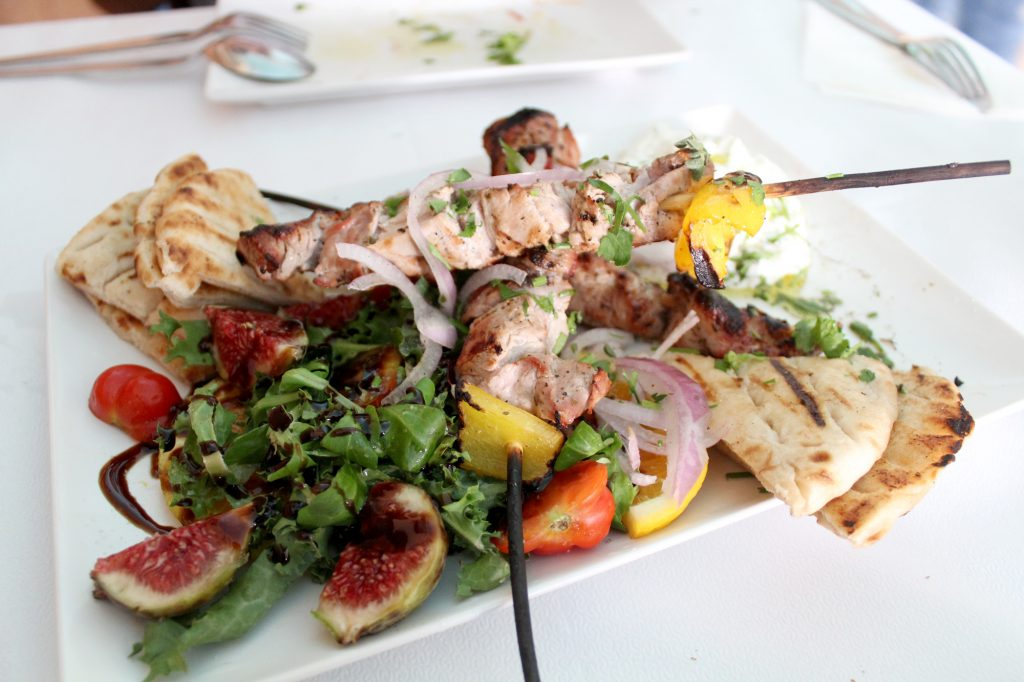 Pork souvlaki with pita bread and tzatziki sauce.
